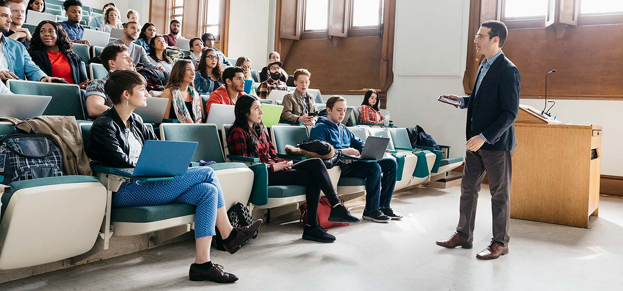 Group of students engaged in lecture hall by their professor