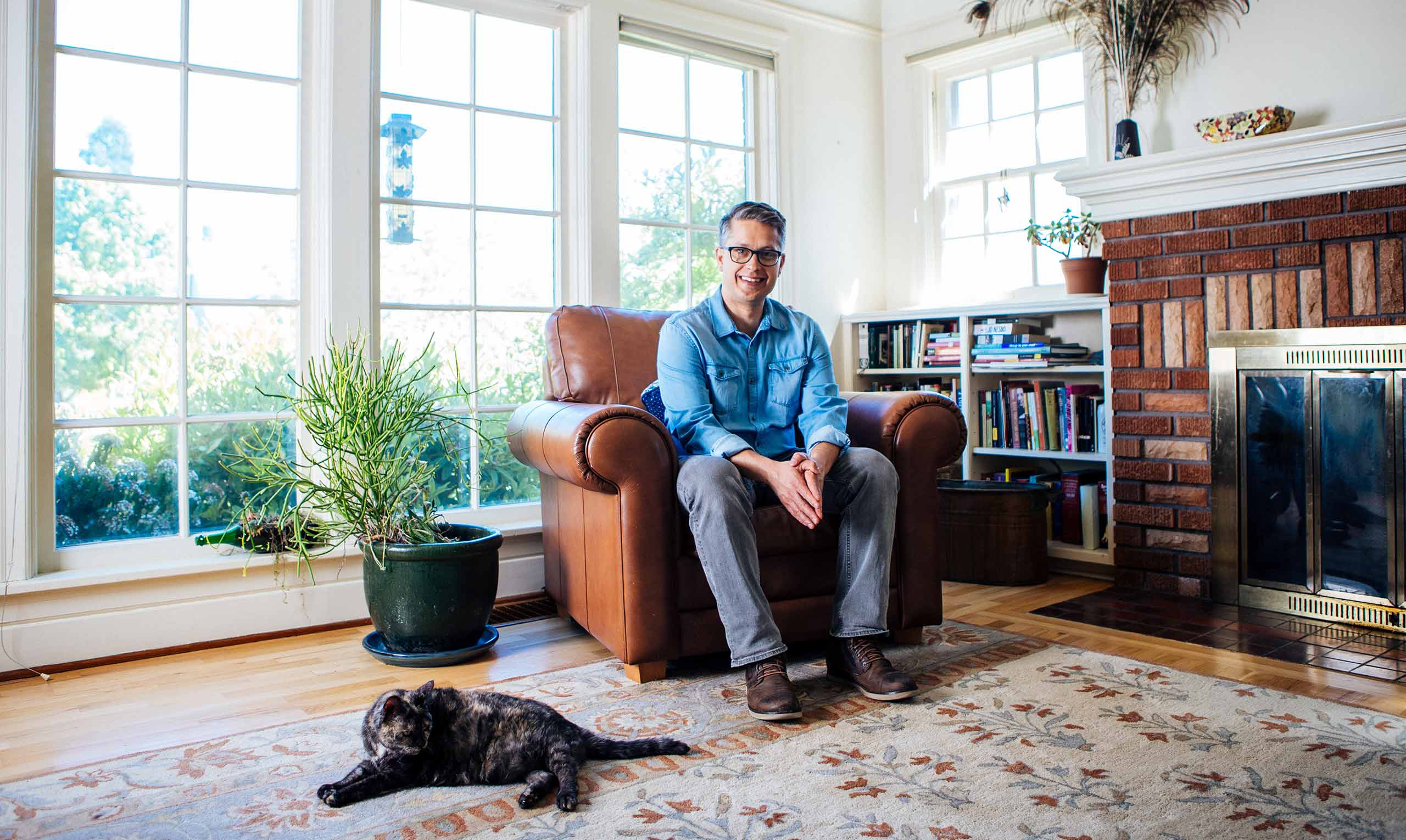 Chris Bone sitting in a comfortable chair in his home