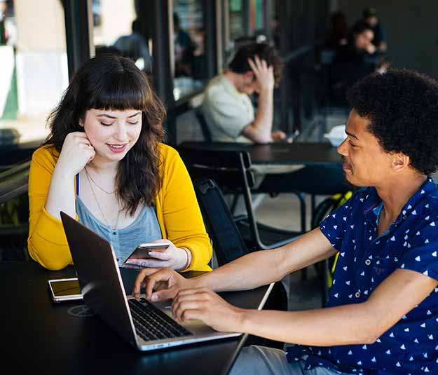 Two students sitting at a cafe on their devices