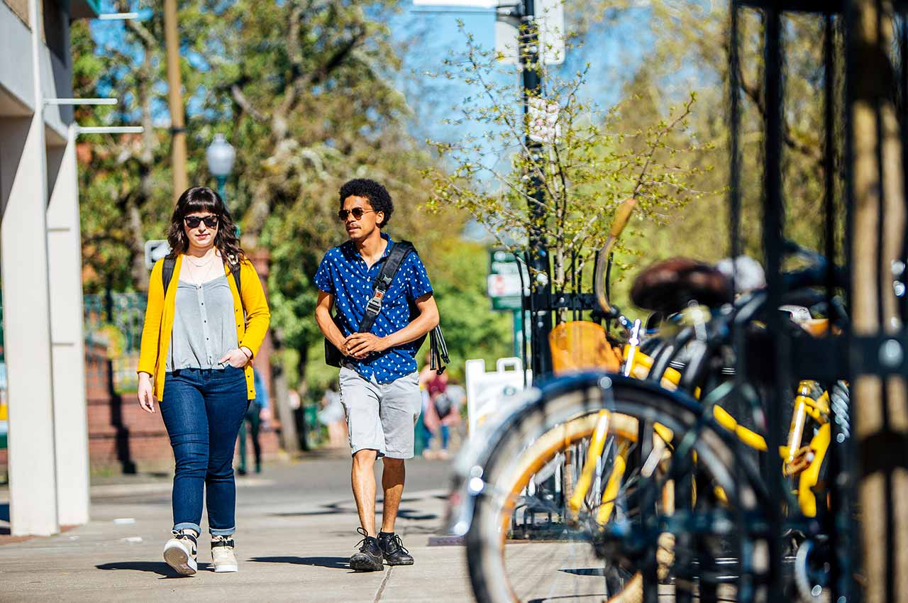Two hip students walking down the street on a sunny day
