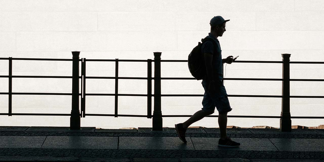 Shaded man walking with phone