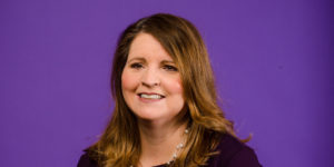Headshot of Andrea Hendricks on a purple background
