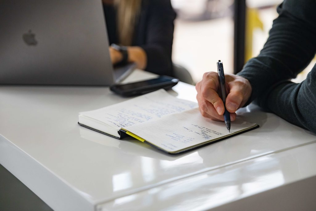 A person's hand is shown up close. They hold a pen in front of an open notebook.